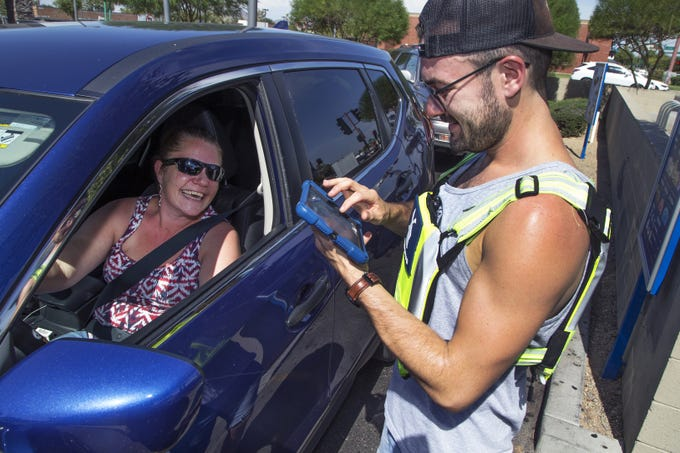 Dutch Bros. employee Ayden Major (right) takes an order from Michell McGarvie, of Avondale, at the Camelback Road and Central Avenue store in Phoenix on July 25, 2018. The company has started using ice vests to cool down their workers who take orders outside in the blazing heat in Phoenix.