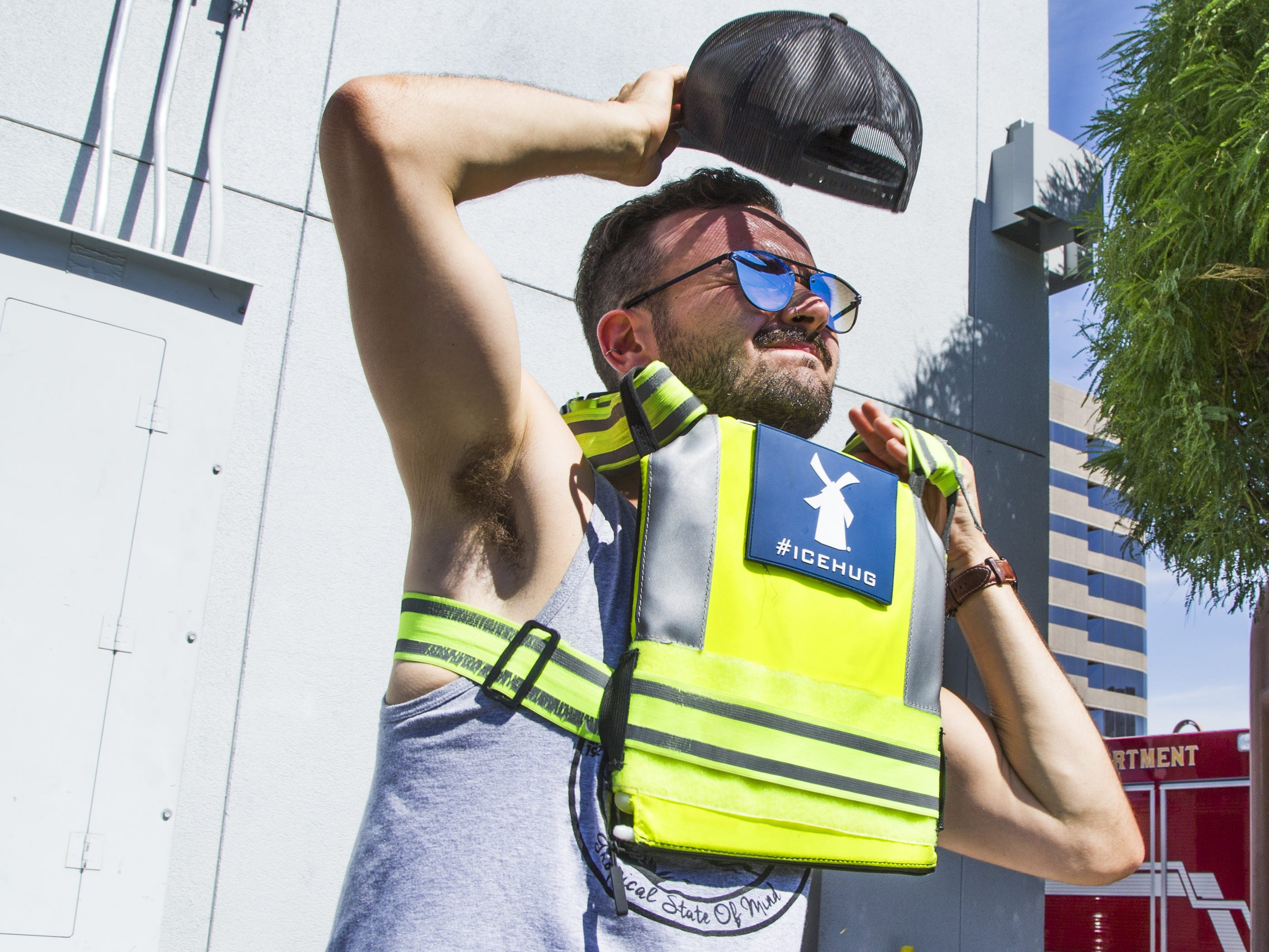 Dutch Bros. employee Ayden Major puts on an ice vest as a way to cool down when taking orders outside in the blazing heat in Phoenix.