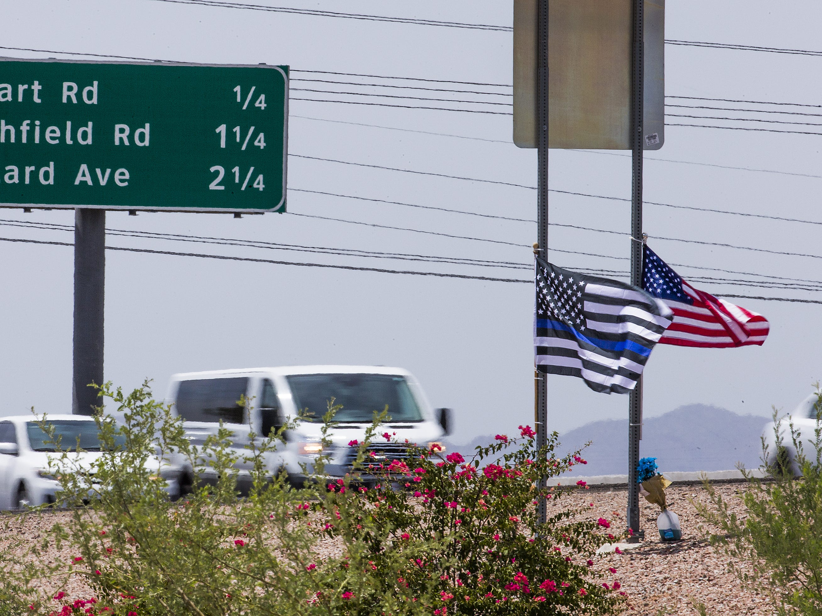 Flowers and flags mark the area where Arizona Department of Public Safety Trooper Tyler Edenhofer was killed and another trooper was shot and injured during an altercation in the eastbound lanes of I-10, west of Avondale Blvd., July 25, 2018.