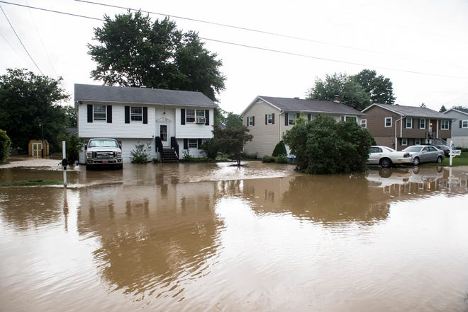 Water flows through a neighborhood on Sherman Road in Penn Township on July 25, 2018.