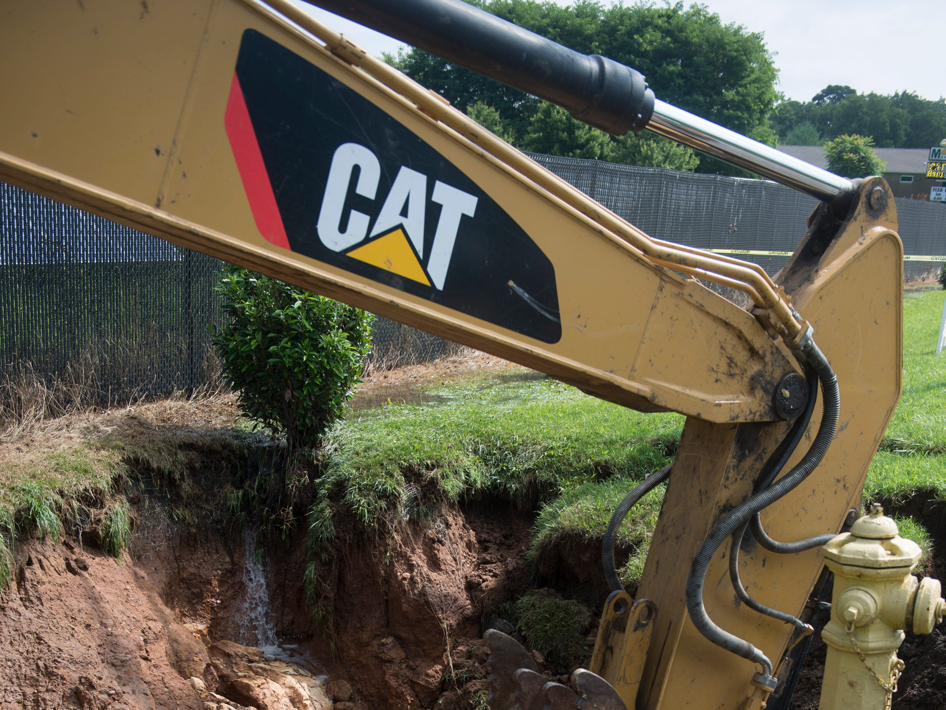 An excavator moves dirt out from a sink hole near Route 30 in Thomasville on July 26, 2018.