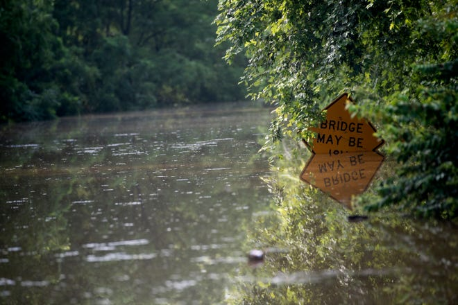 Flooding emerges 616 South to the point that a road sign is barely visible, Thursday, July 26, 2018. Heavy rains poured on the region, closing multiple roads around the county and causing hazards.