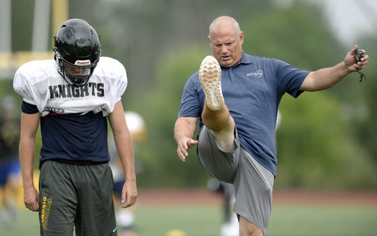 McQuaid punter Jared Campbell, left, gets instruction from kicking coach Sam Watts of Sam Watts Special Teams Academy during a combined summer minicamp with the Irondequoit Eagles at McQuaid Jesuit High School on Wednesday, July 25, 2018.