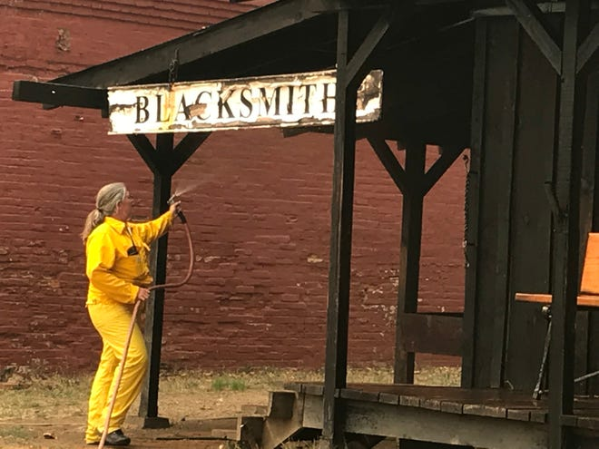 Park superintendent Lori Martin sprays water on the the blacksmith shop at Shasta State Historic Park as the Carr Fire roared toward Shasta on July 26, 2018.
