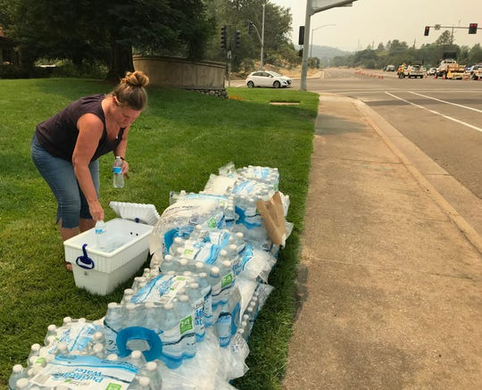 DeAnna Gorisek grabs a bottle of water that was left along with ice for evacuees, firefighters and others outside the Sunset Plaza in Redding on Thursday, July 26, 2018.