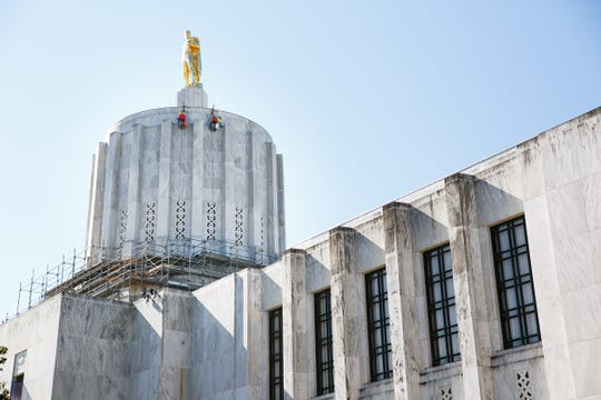 Workers replace old caulking around the marble on the exterior of the Oregon State Capitol on Thursday, July 26, 2018. The work is part of the Capitol Accessibility, Maintenance and Safety project, which was approved by the legislature in 2016 and costs $59.9 million.