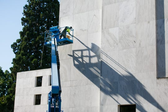 A worker replaces old caulking around the marble on the exterior of the Oregon State Capitol on Thursday, July 26, 2018. The work is part of the Capitol Accessibility, Maintenance and Safety project, which was approved by the legislature in 2016 and costs $59.9 million.