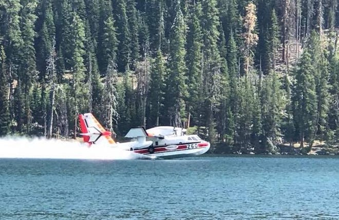 A CL-415 amphibious aircraft scoops water from Mill Lake near the Timber Crater 6 Fire.