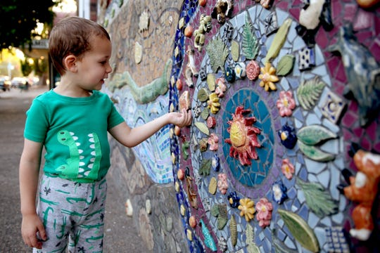Hunter Rawlins, 4, of Salem, feels the tiles on the Peace Mosaic at the downtown Salem YMCA on Wednesday, July 25, 2018. A group of artists and supporters are looking at options for saving the Peace Mosaic when the downtown Salem YMCA is torn down and rebuilt.