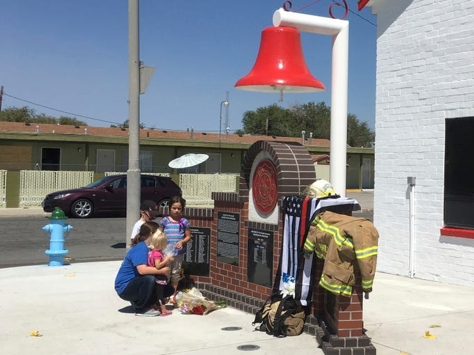 "A woman who would only identify herself as a niece of shooting victim Charles ""Bert"" Miller, is joined by her children as she places flowers at a makeshift memorial Monday, July 23, 2018, in Fallon, Nevada, outside the fire department where Miller was a longtime volunteer firefighter. Police in the northern Nevada city are trying to determine why a 48-year-old man walked into his Mormon church on Sunday, July 22, 2018, and opened fire, killing Miller and injuring another person."