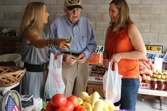 """Shannon Colavecchio, left, and Nanette Schimpf pick up some produce from Lloyd """"Hoot"""" Gibson once he came back to work after being attacked and robbed in 2013."""