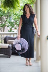 Terry Hendricks wears a black crepe sleeveless wrap-style jumpsuit by Eileen Fisher with Jack Rogers gold cork-wedge shoes and a Frank Olive blush pink hat decorated with black feathers and black satin ribbon.