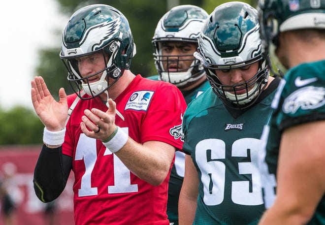 Eagles quarterback Carson Wentz takes part in warm up drills before a recent practice. Wentz is rehabbing from two torn knee ligaments.