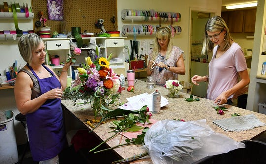 Jenny Hines, right, her mother, Lori Jameson, and Danica Hoffmaster, left, work on floral arrangements at Jameson's Flowers. Hines is a third-generation floral designer and will take over ownership of the family business with her husband, Bryan Hines, next month.
