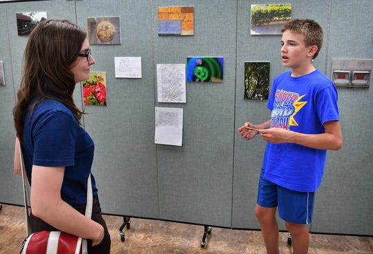 Nicole Welch listens as Dylan DeLozier describes the photograph he exhibited in the Literacy Through Photography pop-up gallery Tuesday at the Wicita Falls Public Library.