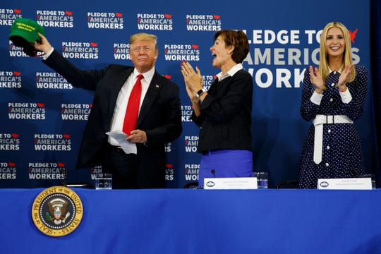 """Ivanka Trump, right, and Gov. Kim Reynolds, R-Iowa, center, look on as President Donald Trump holds up a """"Make Our Farmers Great Again"""" hat during a roundtable discussion on workforce development at Northeast Iowa Community College, Thursday, July 26, 2018, in Peosta, Iowa."""