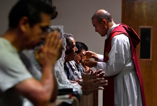 Father Emilio Sosa gives communion during a noon mass at St. Vincent Pallotti Catholic Church in a 2018 file photo.