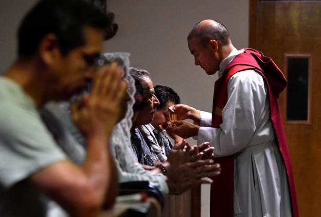 Father Emilio Sosa gives communion during a noon mass at St. Vincent Pallotti Catholic Church Wednesday July 25, 2018. Sosa is the new priest at the church.