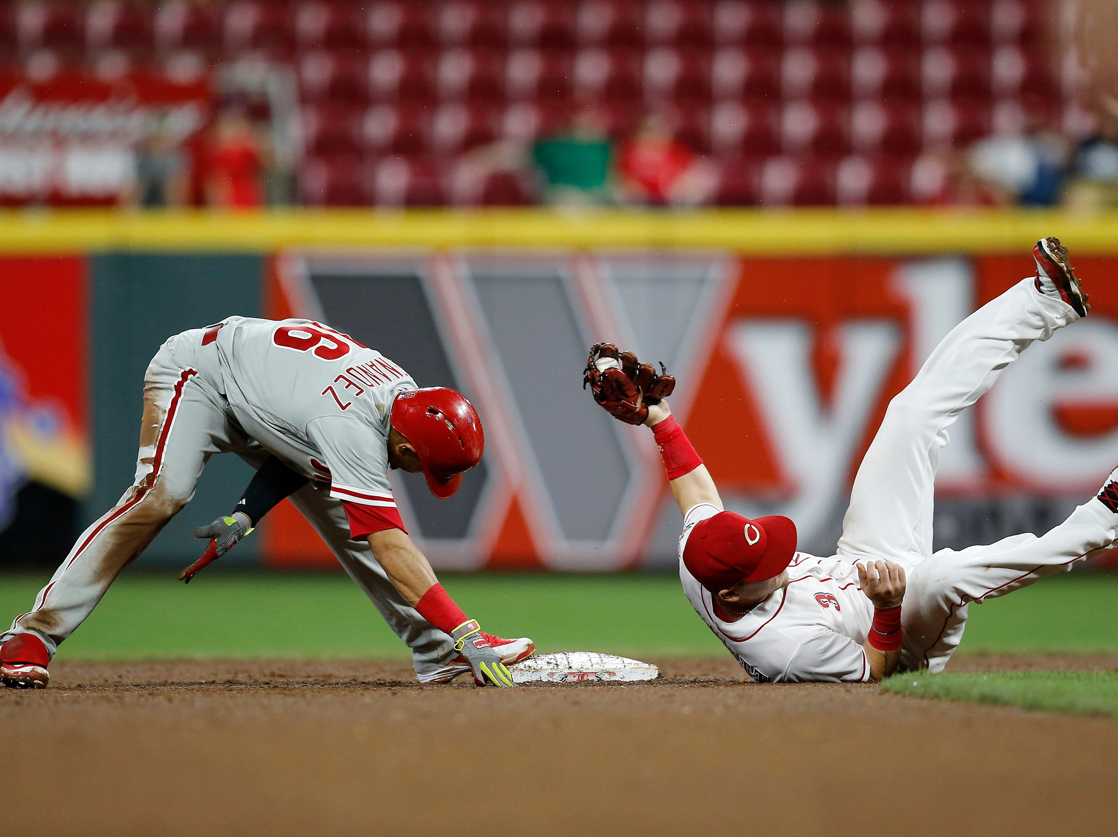 Cincinnati Reds second baseman Scooter Gennett (3) stretches to tag out Philadelphia Phillies second baseman Cesar Hernandez (16) at second base in the top of the eighth inning of the MLB National League game between the Cincinnati Reds and the Philadelphia Phillies at Great American Ball Park in downtown Cincinnati on Thursday, July 26, 2018. The Reds lost 9-4.