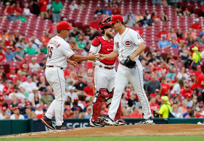 Cincinnati Reds interim manager Jim Riggleman (35) takes the ball from starting pitcher Tyler Mahle (30) as he leaves the game in the top of the second inning of the MLB National League game between the Cincinnati Reds and the Philadelphia Phillies at Great American Ball Park in downtown Cincinnati on Thursday, July 26, 2018. The Reds trailed 4-2 after three innings.
