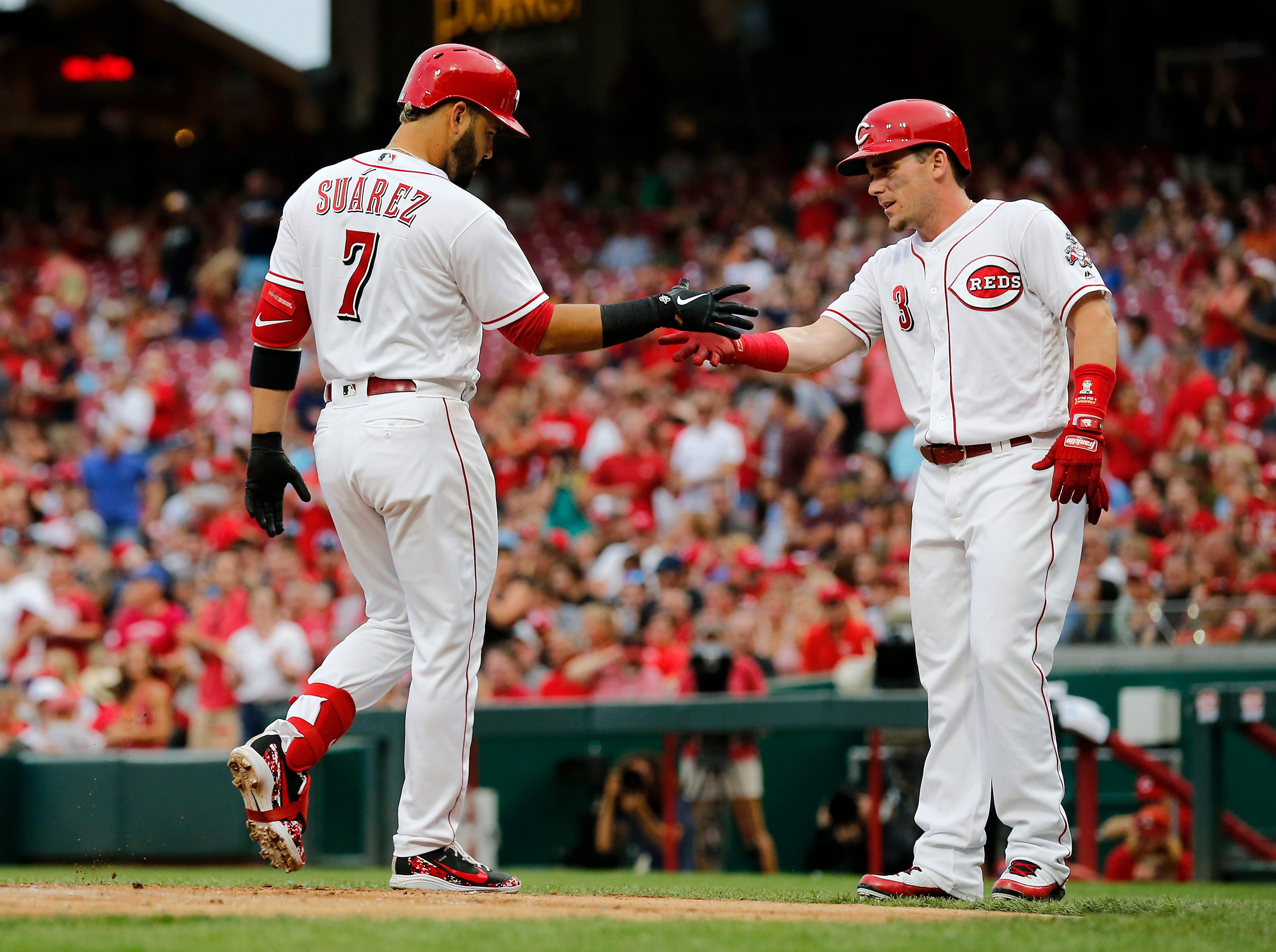 Cincinnati Reds third baseman Eugenio Suarez (7) and second baseman Scooter Gennett (3) shake hands after Suarez's two-run home run in the bottom of the first inning of the MLB National League game between the Cincinnati Reds and the Philadelphia Phillies at Great American Ball Park in downtown Cincinnati on Thursday, July 26, 2018. The Reds trailed 4-2 after three innings.
