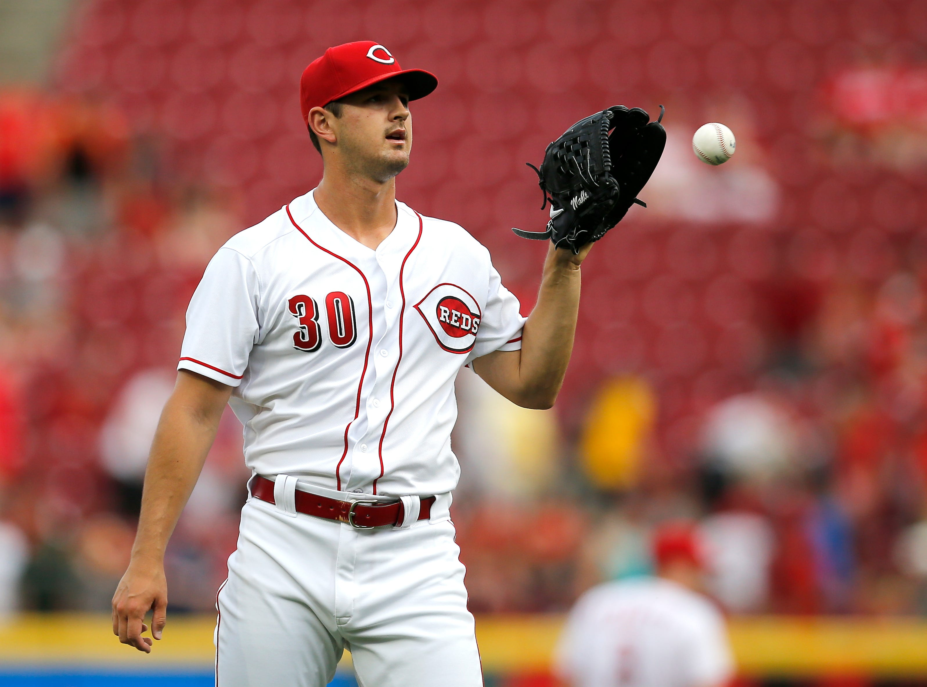Cincinnati Reds starting pitcher Tyler Mahle (30) gets a new ball after giving up a two-run home run to Philadelphia Phillies first baseman Carlos Santana (41) in the top of the first inning of the MLB National League game between the Cincinnati Reds and the Philadelphia Phillies at Great American Ball Park in downtown Cincinnati on Thursday, July 26, 2018. The Reds trailed 4-2 after three innings.