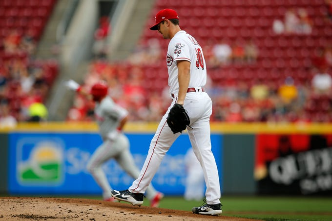 Cincinnati Reds starting pitcher Tyler Mahle (30) circles back to the mound after giving up a home run to Philadelphia Phillies left fielder Rhys Hoskins (17) in the top of the first inning of the MLB National League game between the Cincinnati Reds and the Philadelphia Phillies at Great American Ball Park in downtown Cincinnati on Thursday, July 26, 2018. The Reds trailed 4-2 after three innings.