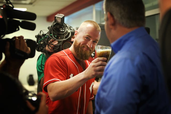 Cincinnati Reds catcher, Tucker Barnhart, holds out the 'ceremonial pour' of Coke at the Frisch's Mainliner, in Fairfax, on Friday morning. Frisch's is making the switch back to Coke products after carrying Pepsi since 2013.
