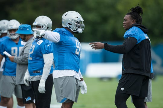 Lions defensive tackle A'Shawn Robinson, center left, talks to defensive end Ziggy Ansah during training camp in Allen Park on Friday, July 27, 2018.
