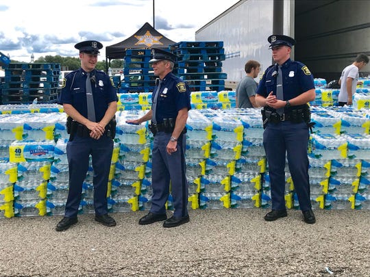 Michigan State Police troopers help hand out bottled water at Parchment High School in Parchment, Michigan.