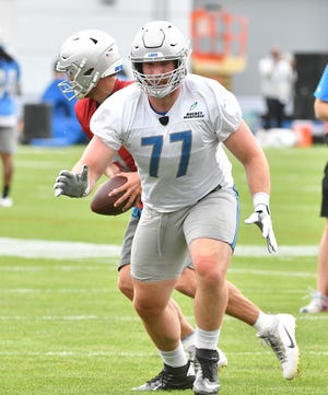 Lions quarterback Matthew Stafford in shotgun position with rookie offensive lineman Frank Ragnow on the line defending during drills.