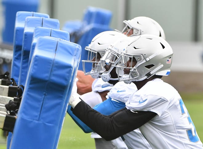 Lions rookie Kerryon Johnson and the running backs hit the sled during drills.