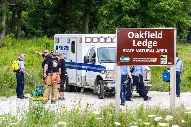 Members of Lifestar Ambulance Service and Oakfield first responders get ready to enter a wooded area Friday at the Oakfield Ledge State Nature Area, southwest of Oakfield, to search for a man who had fallen off one of the cliffs.