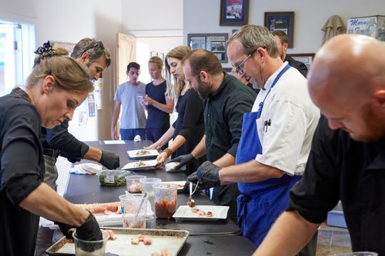 Jason Shaeffer and his crew plate dishes of honey lime cured yellowtail at the second summer Secret Supper at the Howling Cow Cafe, on Thursday, July 26, 2018.