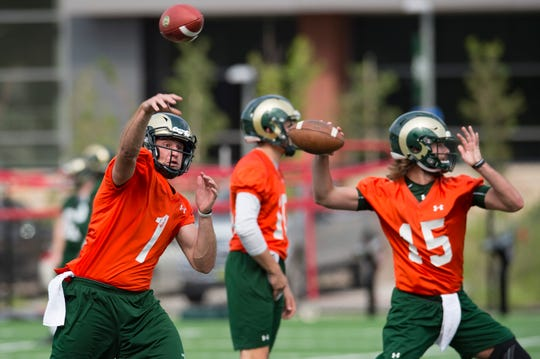 CSU quarterback K.J. Carta-Samuels, left, throws the ball during the Rams' first practice of the season outside of Canvas Stadium on Friday, July 27, 2018.