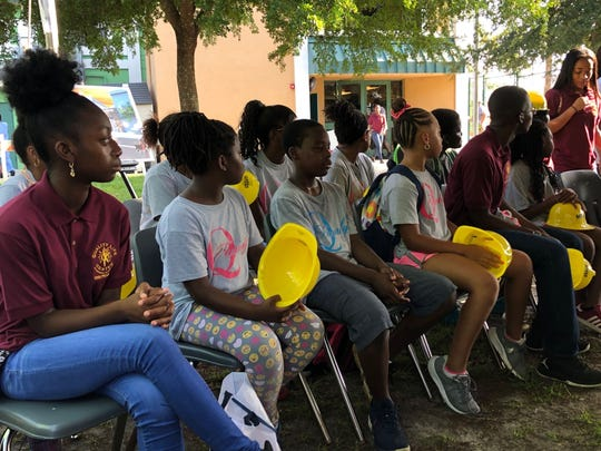 Quality Life Center children listen to speakers to the ceremonial ground-breaking ceremonies for a center expansion.