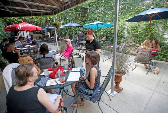 Vine-covered brick walls, strings of lights and colorful umbrellas add to the ambiance of Piazza Angelina, the outdoor dining patio at Angelina restaurant.