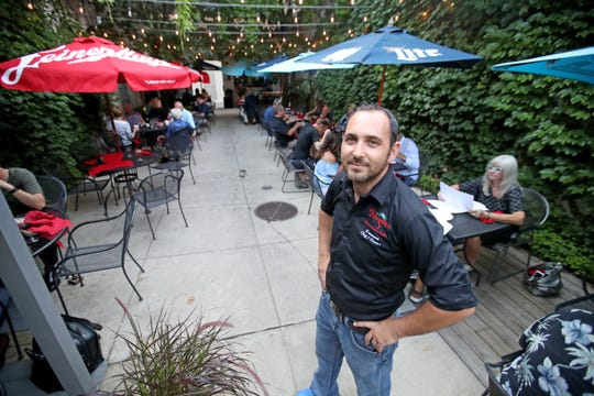 Ermanno Cervantes, executive chef and owner of Angelina, is pictured in 2018 in the intimate outdoor patio of his Italian restaurant in downtown Green Bay.