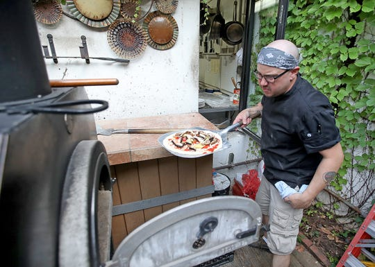 Sous chef Nate Arbuckle puts a handmade pizza into the outdoor wood-fired oven at Angelina. The 700-degree oven can bake a pizza in 2 minutes.