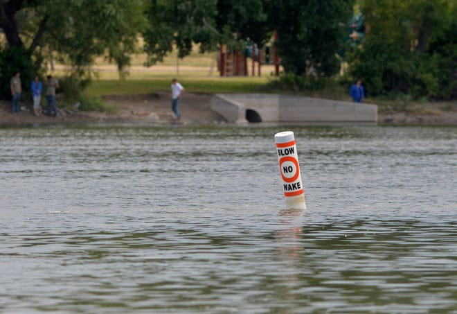 """A series of """"No Wake"""" bouys line the western bank of Broadwater Bay just below the mouth of the Sun River to remind boaters to slow down."""