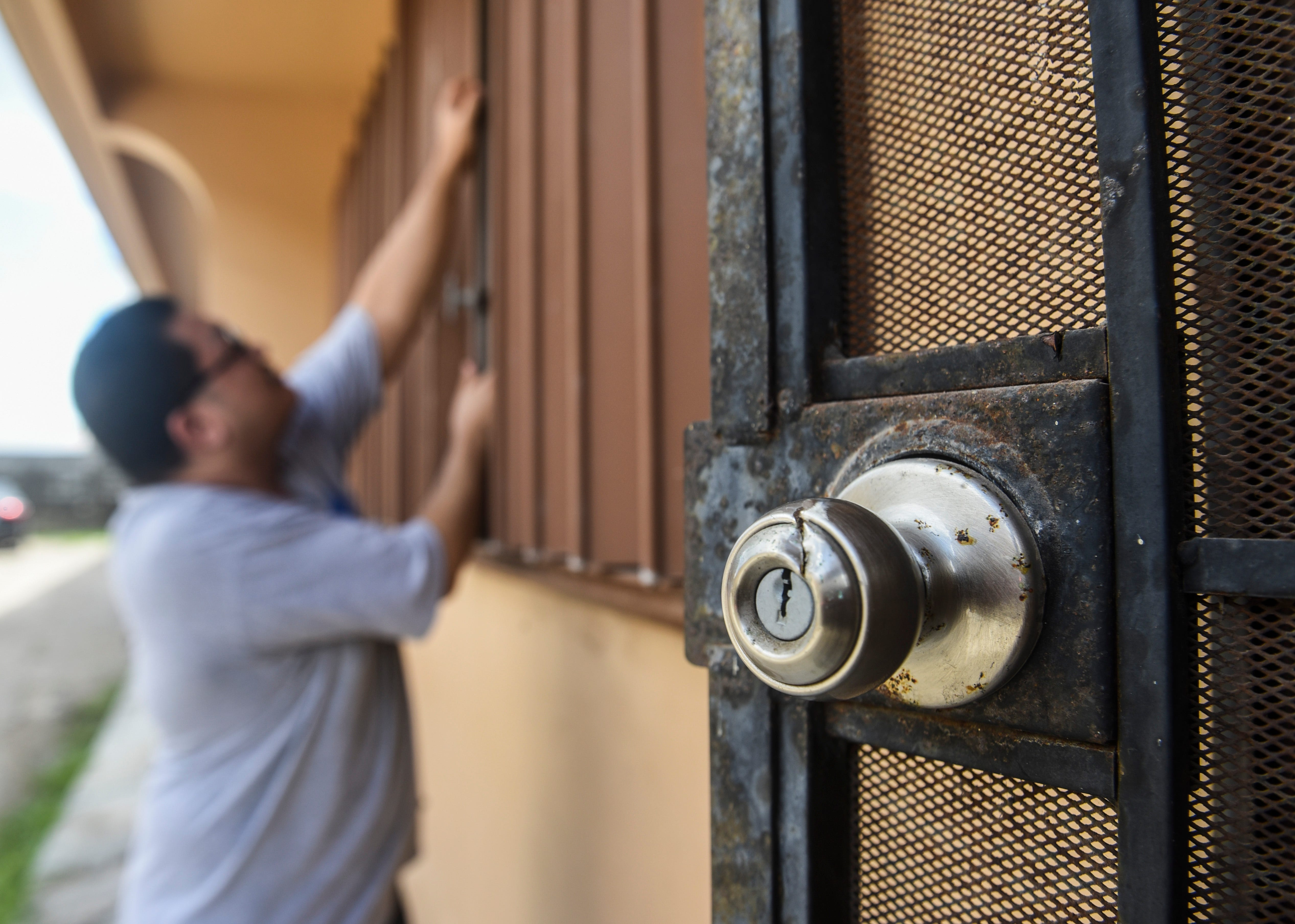 Joseph Tuvera, 36, GNN Apartment resident, closes a window shutter to his unit in Harmon on Friday, July 27, 2018. Tuvera said damage seen on the knob and frame of the security door, right, were due to a machete-wielding youth who chased after him and his mother during the early morning hours of Thursday, July 26.