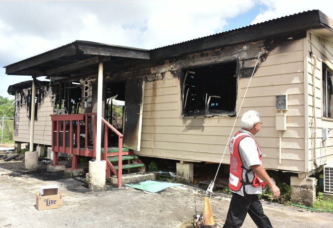 David Peredo, disaster program manager of the American Red Cross Guam Chapter, looks at the house in the Harmon Industrial Park on Friday, July 27, 2018, day after a fire destroyed it. Peredo said the Red Cross was trying to reach out to the family of the man who died, and surviving residents of the house without luck as of Thursday.