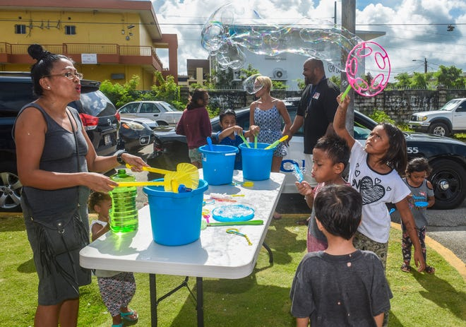 Children, living at the Hemlani's Harmon Apartments, play with bubble wands during a Power of Play outreach event on Friday, July 27, 2018.