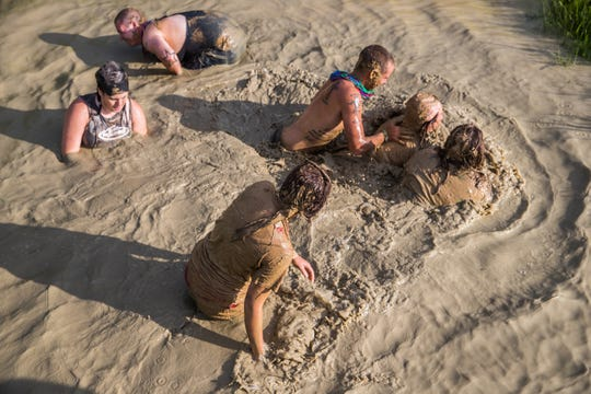 Redneck Rave participants wash off in a water hole at BlackSwan Mudpit in Medora, Ind., on Friday, July 20, 2018.