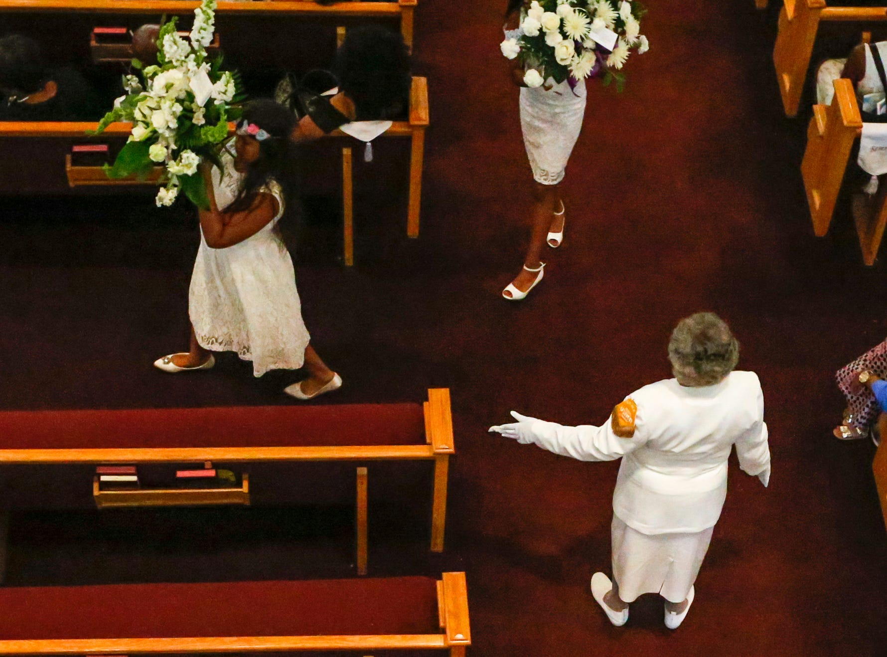 An usher directs young children outside before the pallbearers prepare to remove the caskets from the  homegoing service of Glenn Coleman, 40, Reece, 9, Evan, 7, and Arya, 1, at Grace Apostolic Church on Friday, July 27, 2018. Seventeen people were killed in the duck boat accident in Branson, Missouri, nine of them were members of the Coleman family.