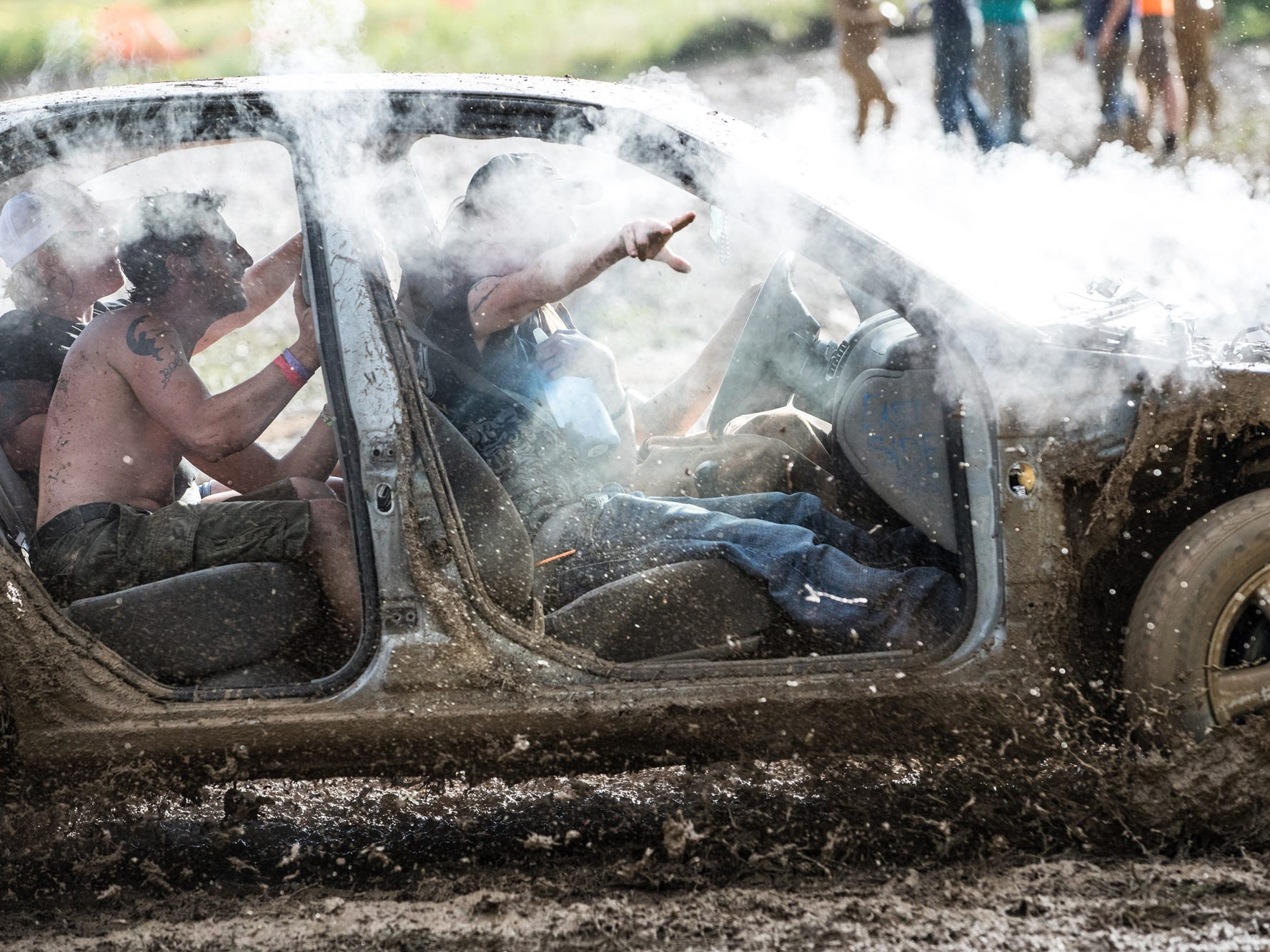 Four people take a small, torn down car through the mud pit during the Redneck Rave at BlackSwan Mudpit in Medora, Ind., on Friday, July 20, 2018.