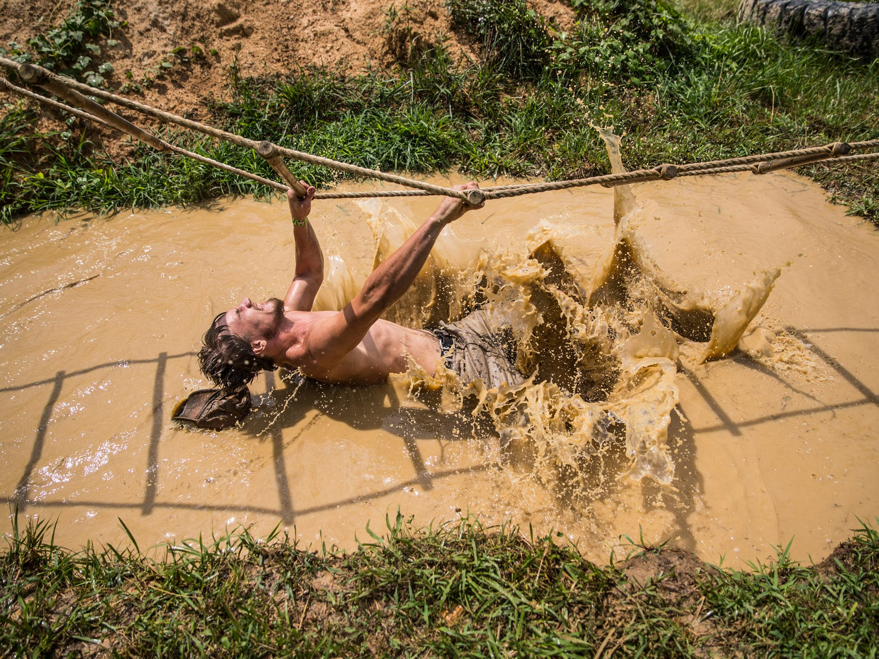 Ethan Taylor, of Middletown, Ohio, loses his balance and falls in a water hole during the Redneck Rave at BlackSwan Mudpit in Medora, Ind., on Friday, July 20, 2018.