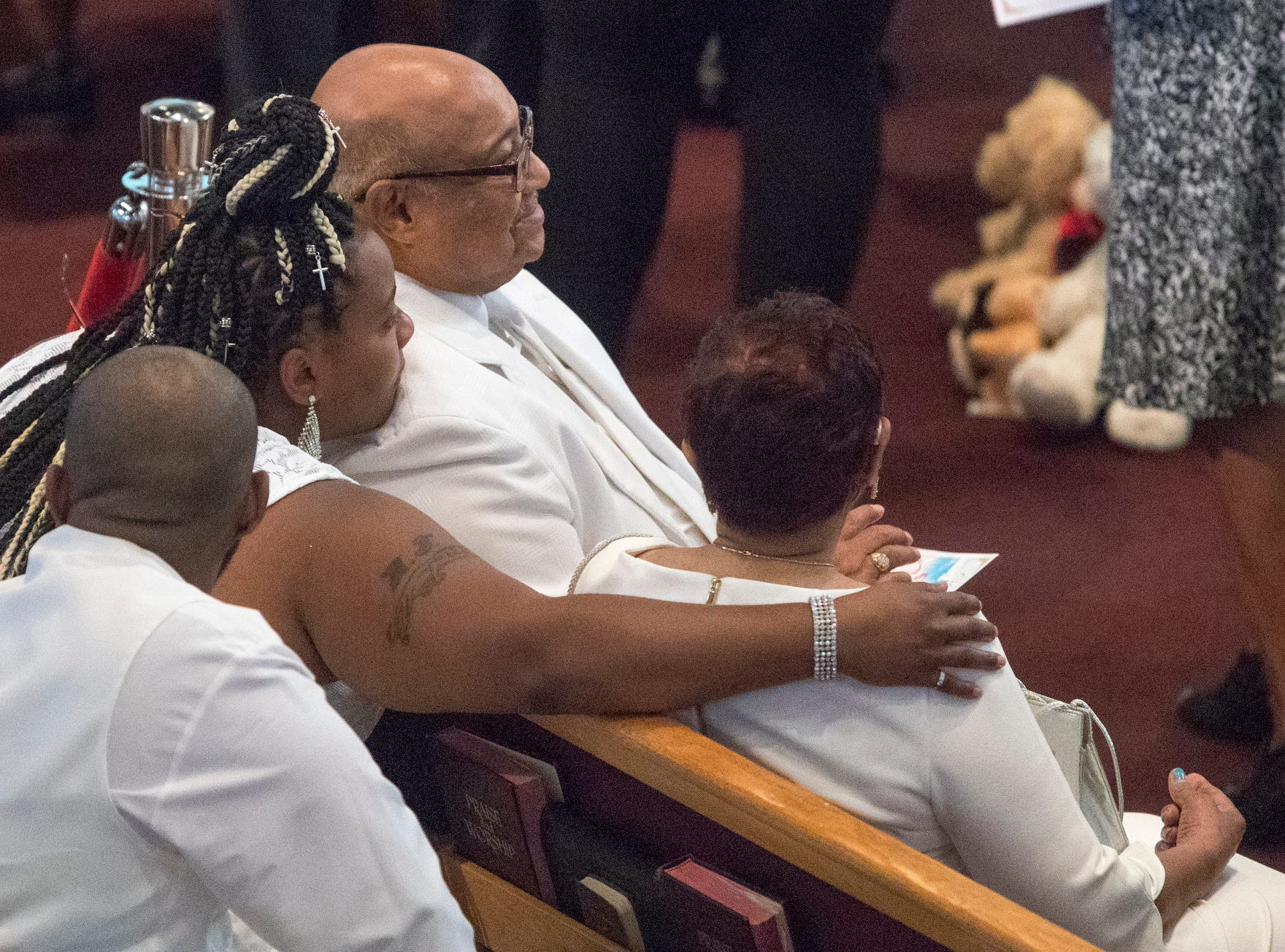 Family and friends watch others view the casket before the homegoing service of Glenn Coleman, 40, Reece, 9, Evan, 7, and Arya, 1, at Grace Apostolic Church on Friday, July 27, 2018. Seventeen people were killed in the duck boat accident in Branson, Missouri, nine of them were members of the Coleman family.