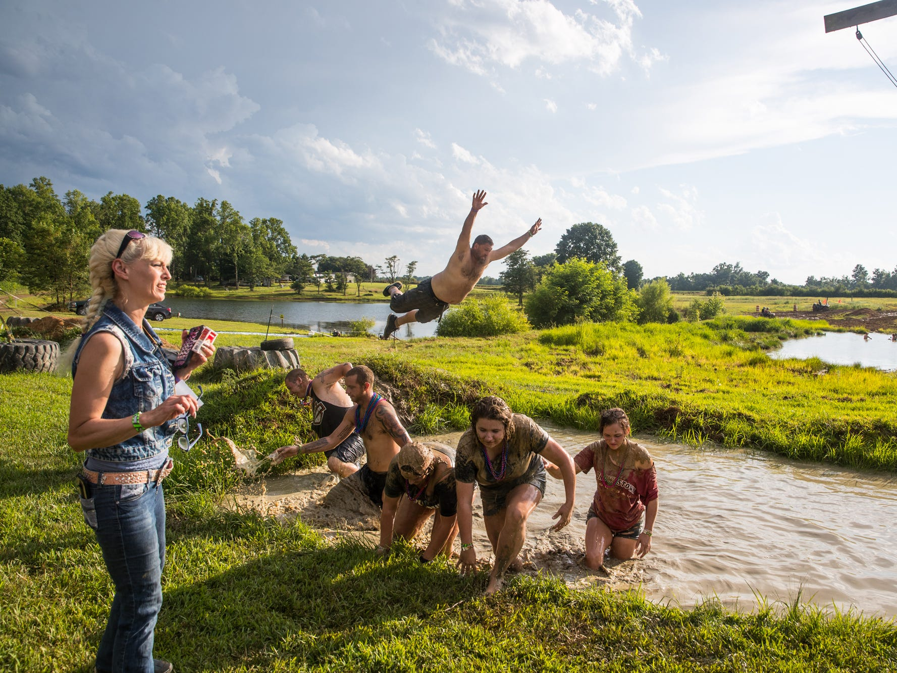 Participants swim and wash off mud in a water hole during the Redneck Rave at BlackSwan Mudpit in Medora, Ind., on Friday, July 20, 2018.