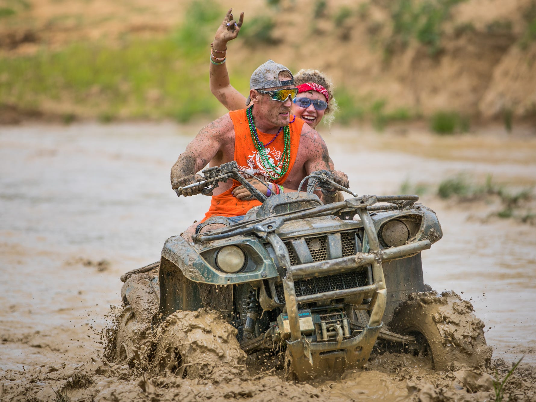 ATV riders make it through the largest of three mud pits during the Redneck Rave at BlackSwan Mudpit in Medora, Ind., on Friday, July 20, 2018.